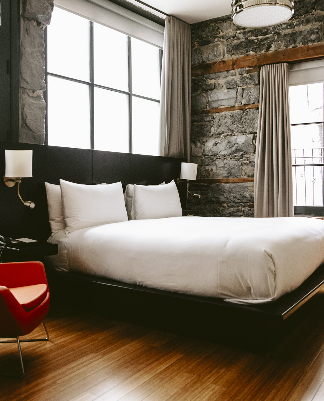 A bed in front of a stone wall and a window in one of the rooms of Le Petit Hôtel.