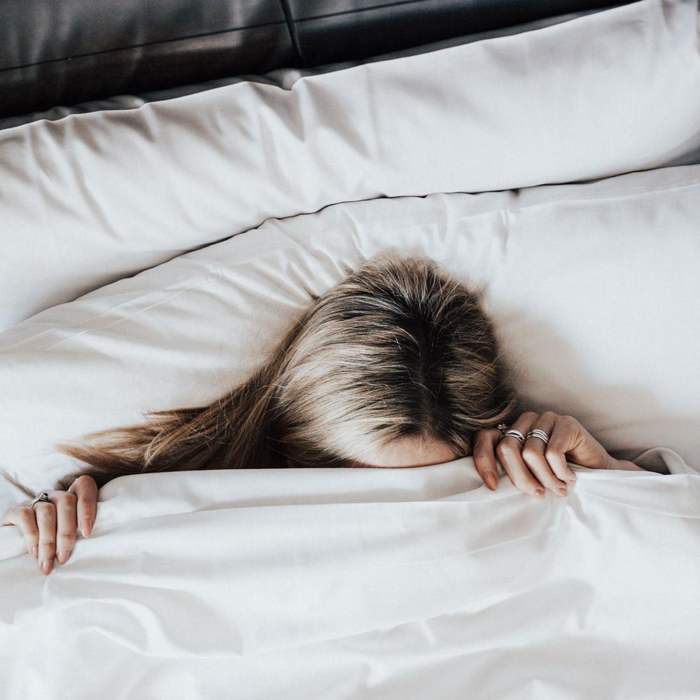 Une femme se cachant dans les drats d'un lit du Petit Hôtel.