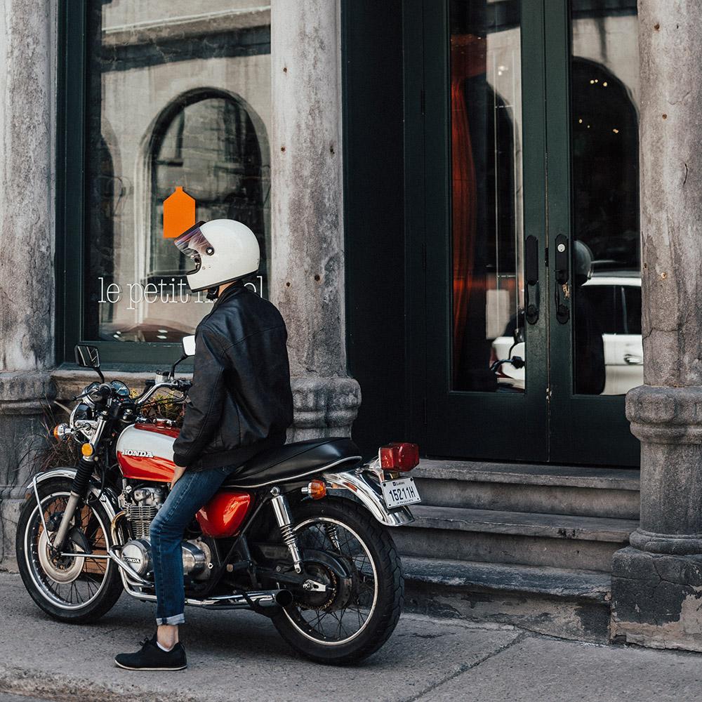 Un homme sur sa moto rouge et noire en face de l'entrée du Petit Hôtel.