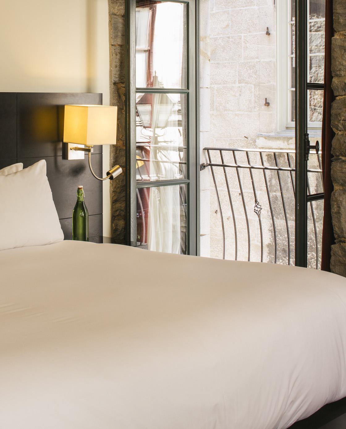 Un lit et une fenêtre ouverte sur l'extérieur dans une des chambres du Petit Hôtel.