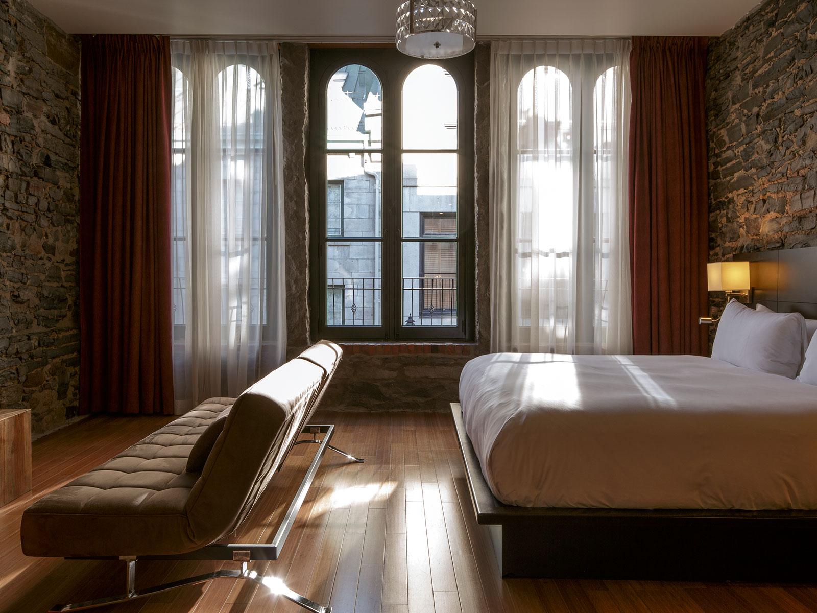 Un futon noir en face d'un lit dans l'une des chambres du Petit Hôtel.