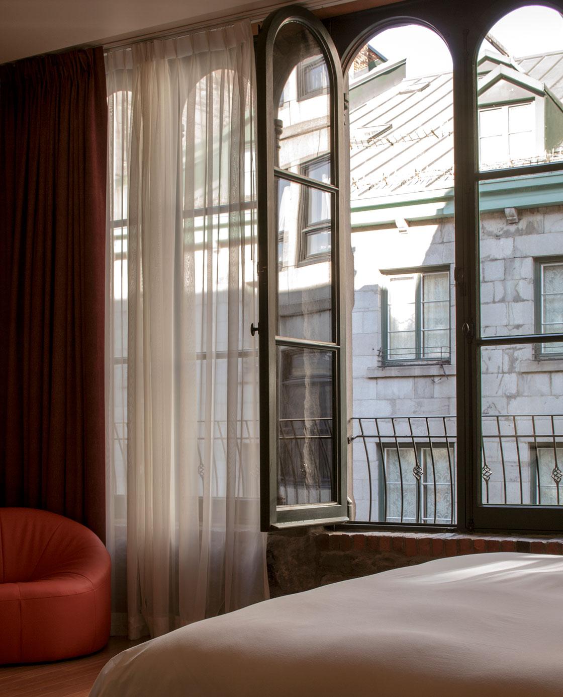 Un fauteuil orange et un lit devant une fenêtre ouverte sur l'extérieur dans une des chambres du Petit Hôtel.