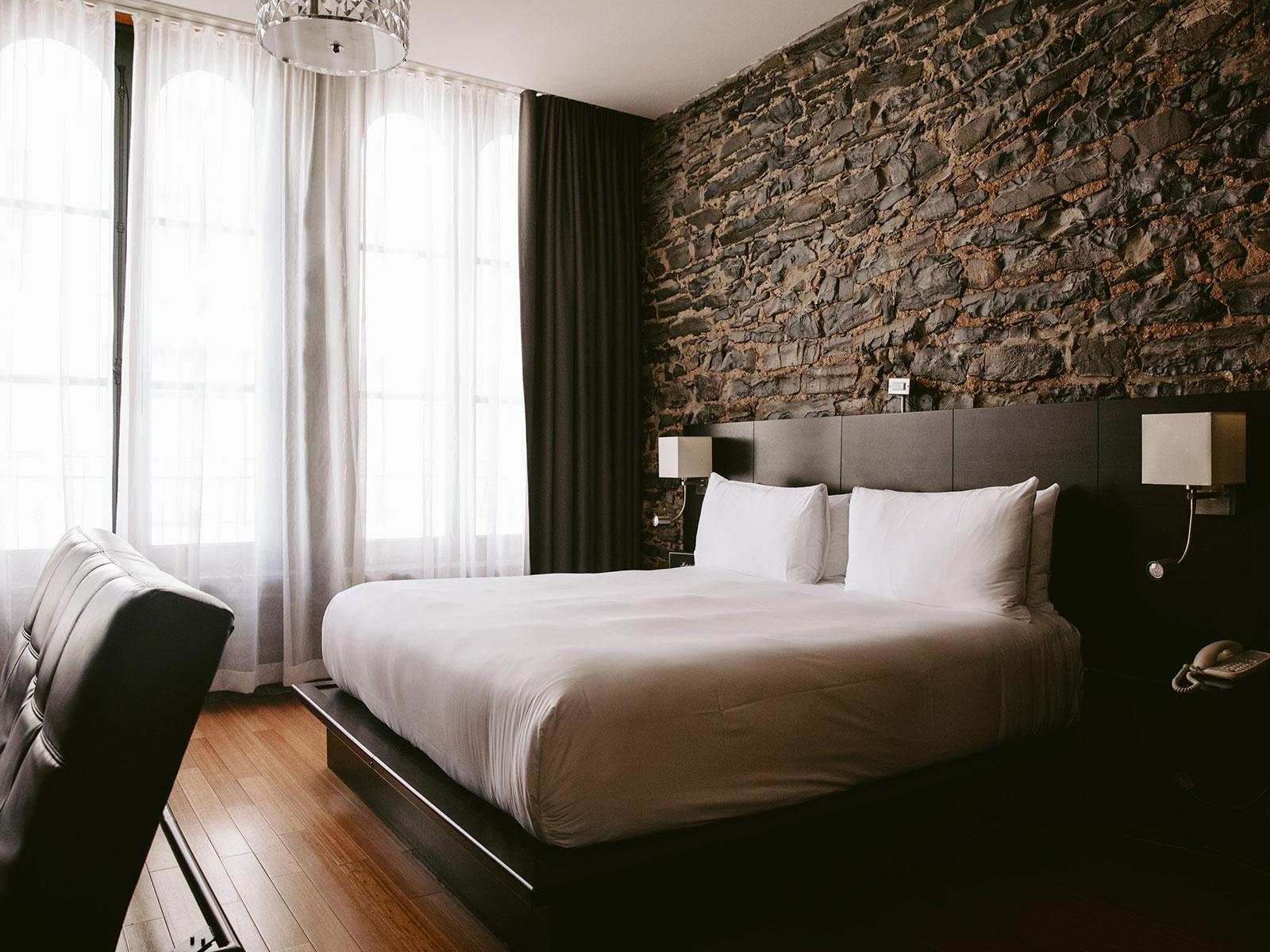 Un lit devant un mur de pierres dans une des chambres du Petit Hôtel.