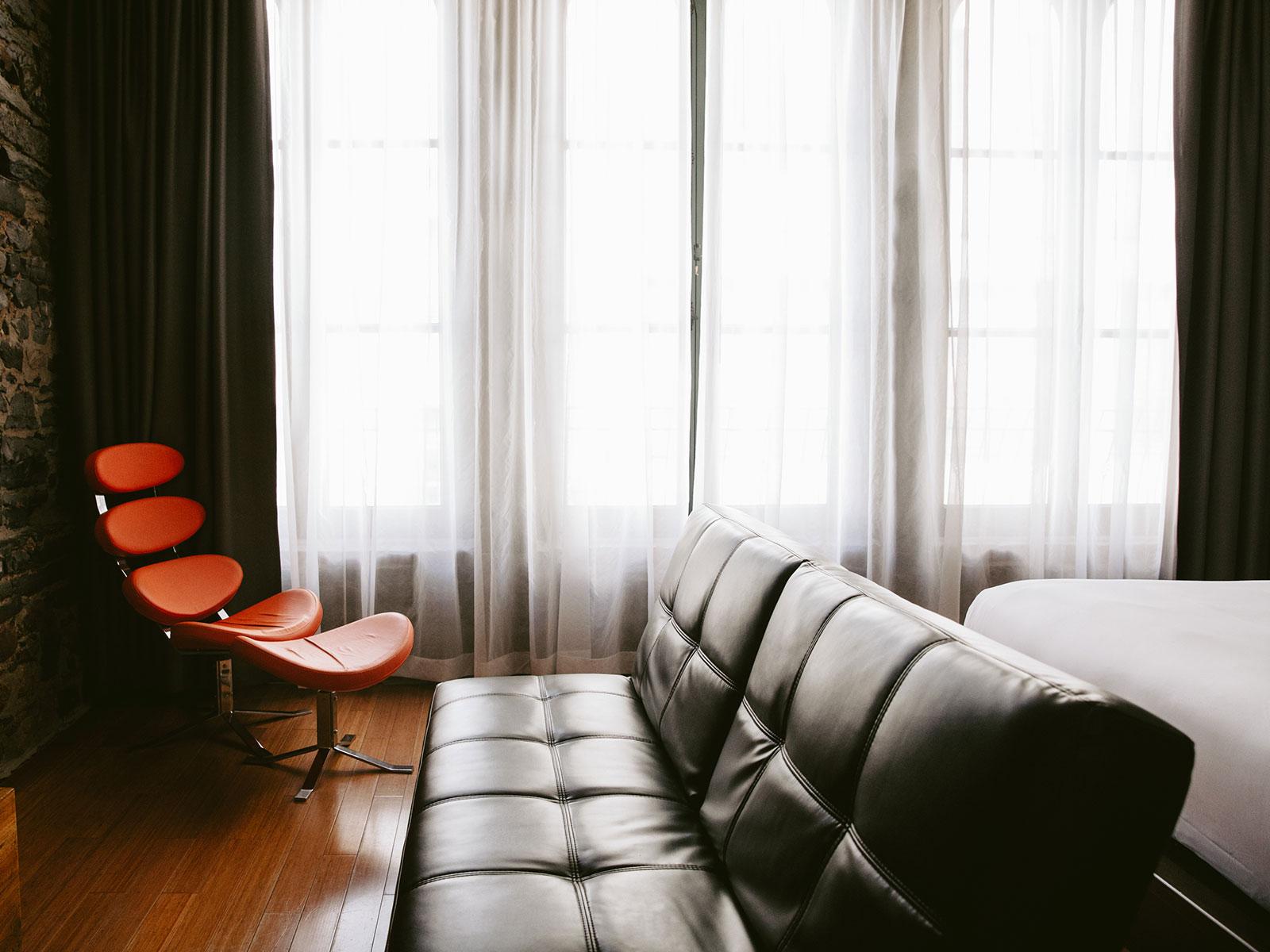 Un futon noir et une chaise orange en face d'un lit dans l'une des chambres du Petit Hôtel.