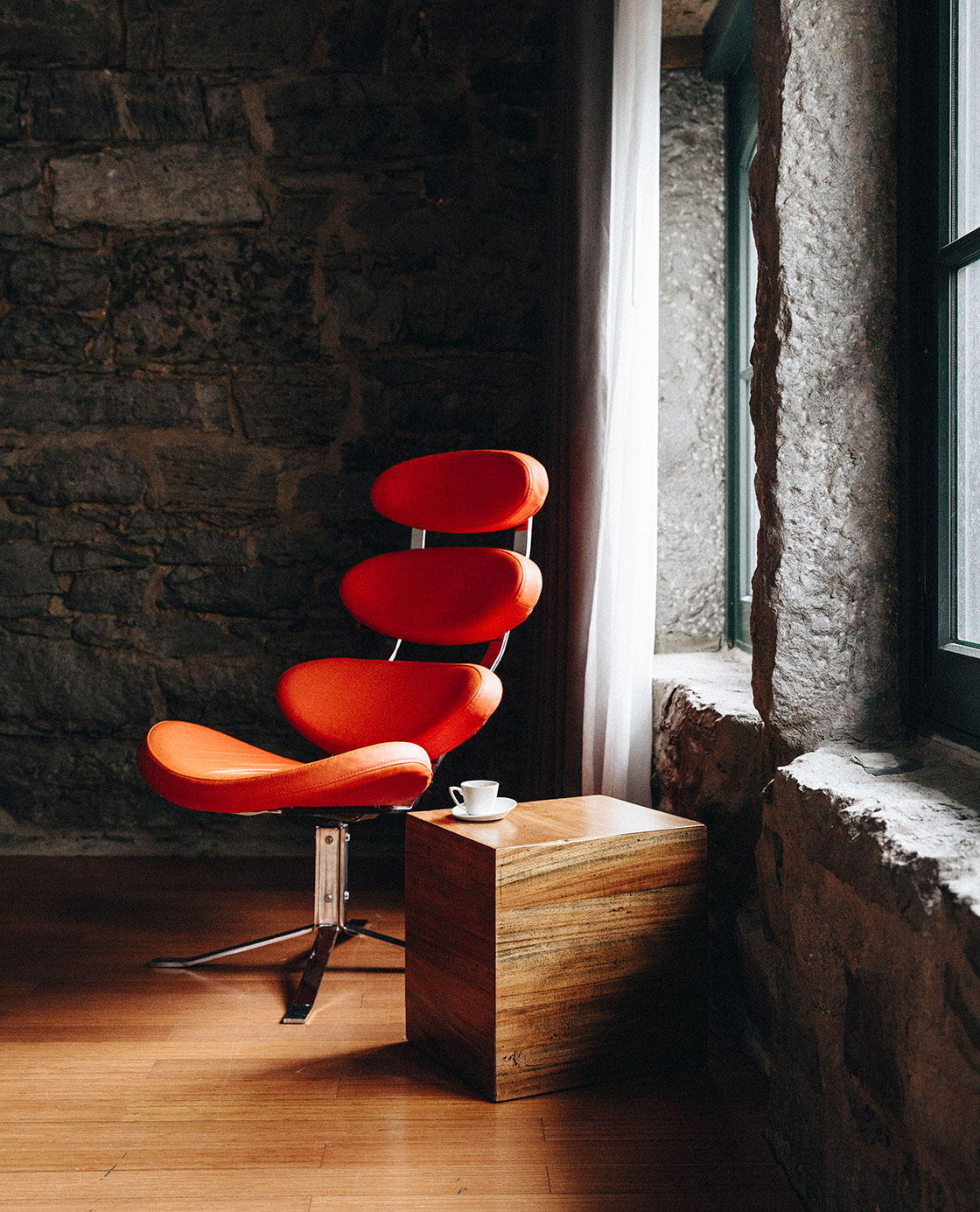 Un fauteuil orange et un tasse de café posée sur une table en boisdans une des chambres du Petit Hôtel.