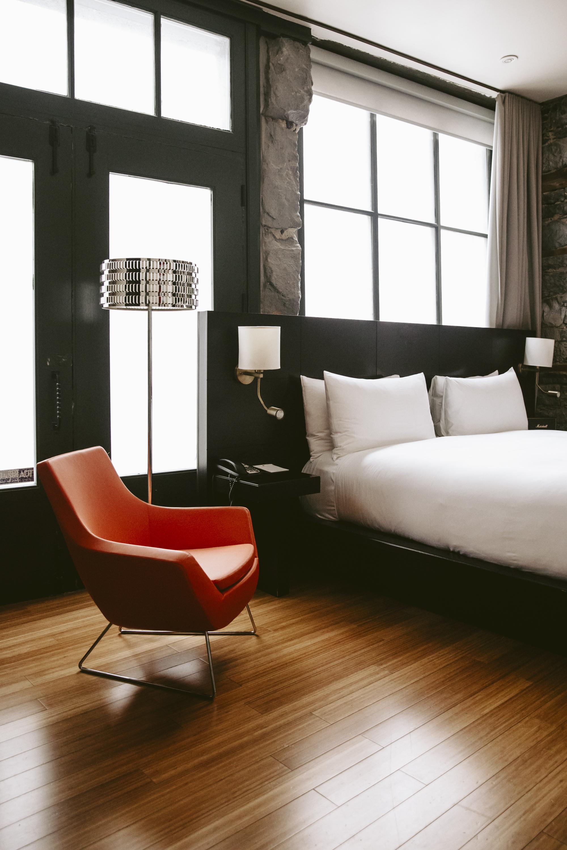 Un fauteuil orange, un lampadaire et un lit devant une fenêtre dans l'une des chambres du Petit Hôtel.