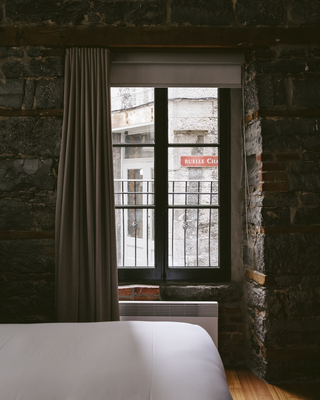Un lit et la vue sur une fenêtre et un mur en pierres dans une des chambres du Petit Hôtel.