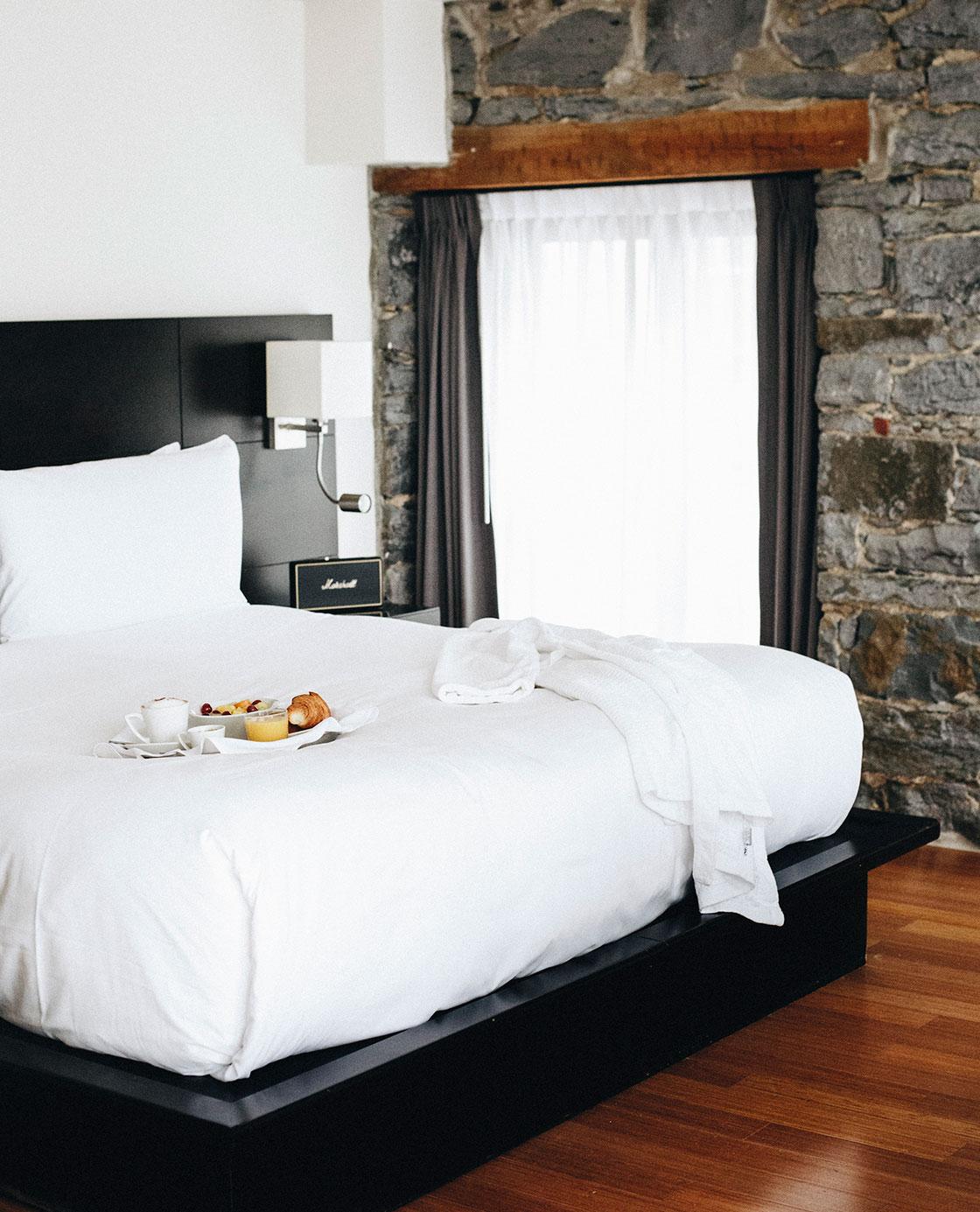 Un plateau de petit-déjeuner et une serviettes posés sur un lit.