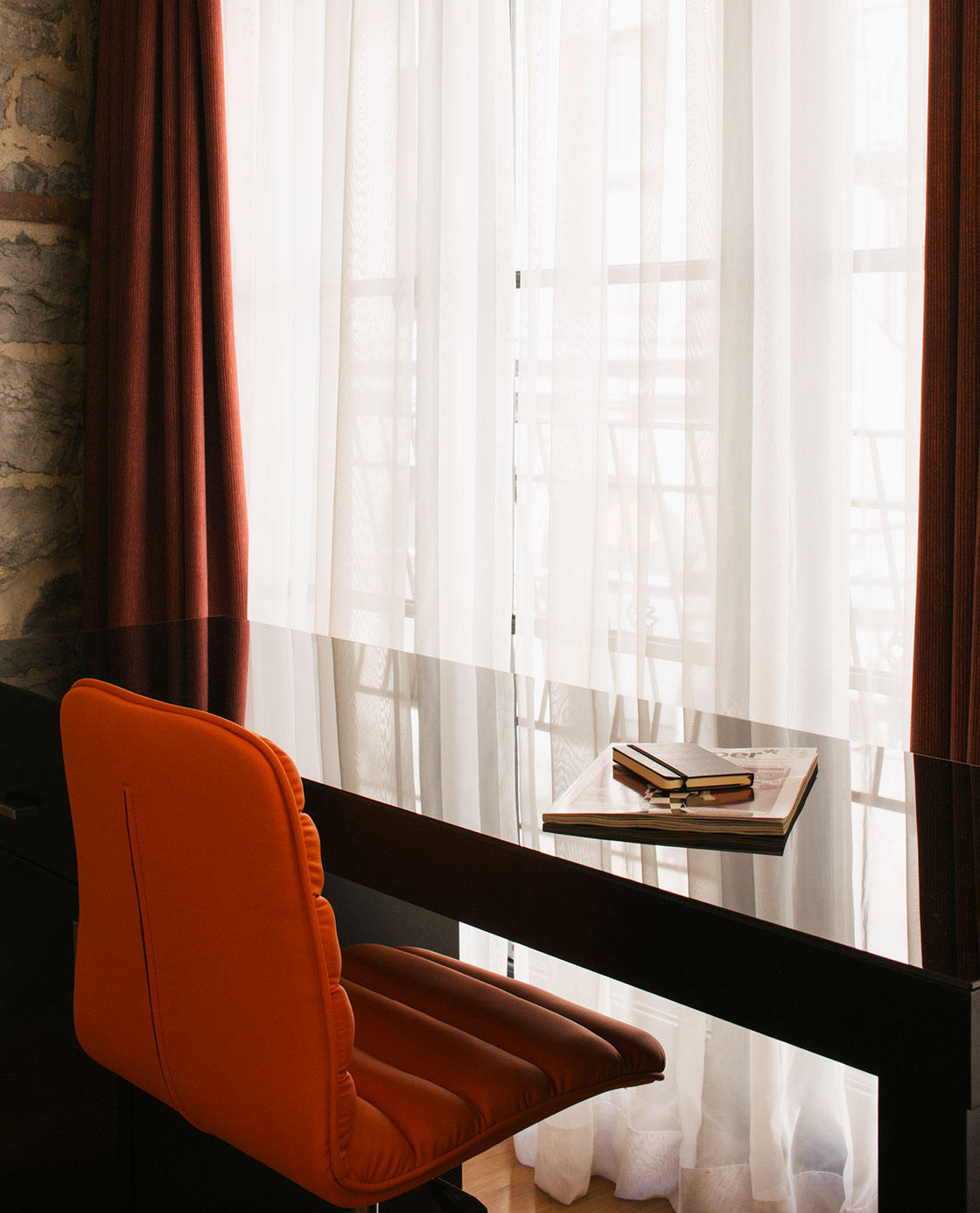 An orange chair and desk in front of a window