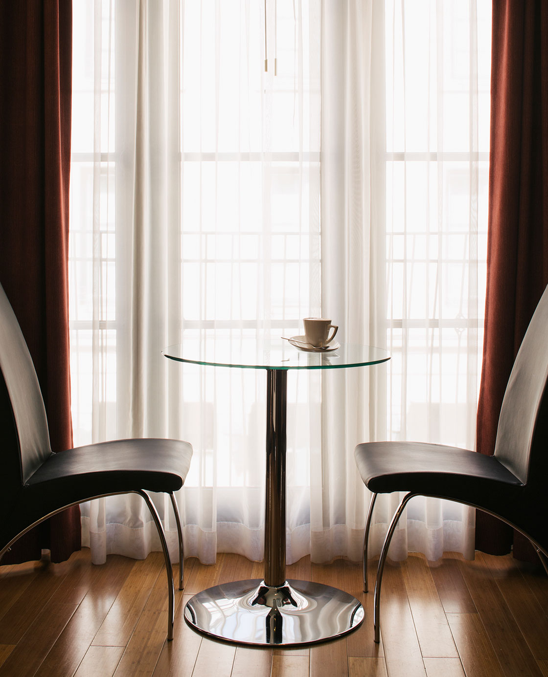 Two chairs in front of a glass table with a coffee on the table.