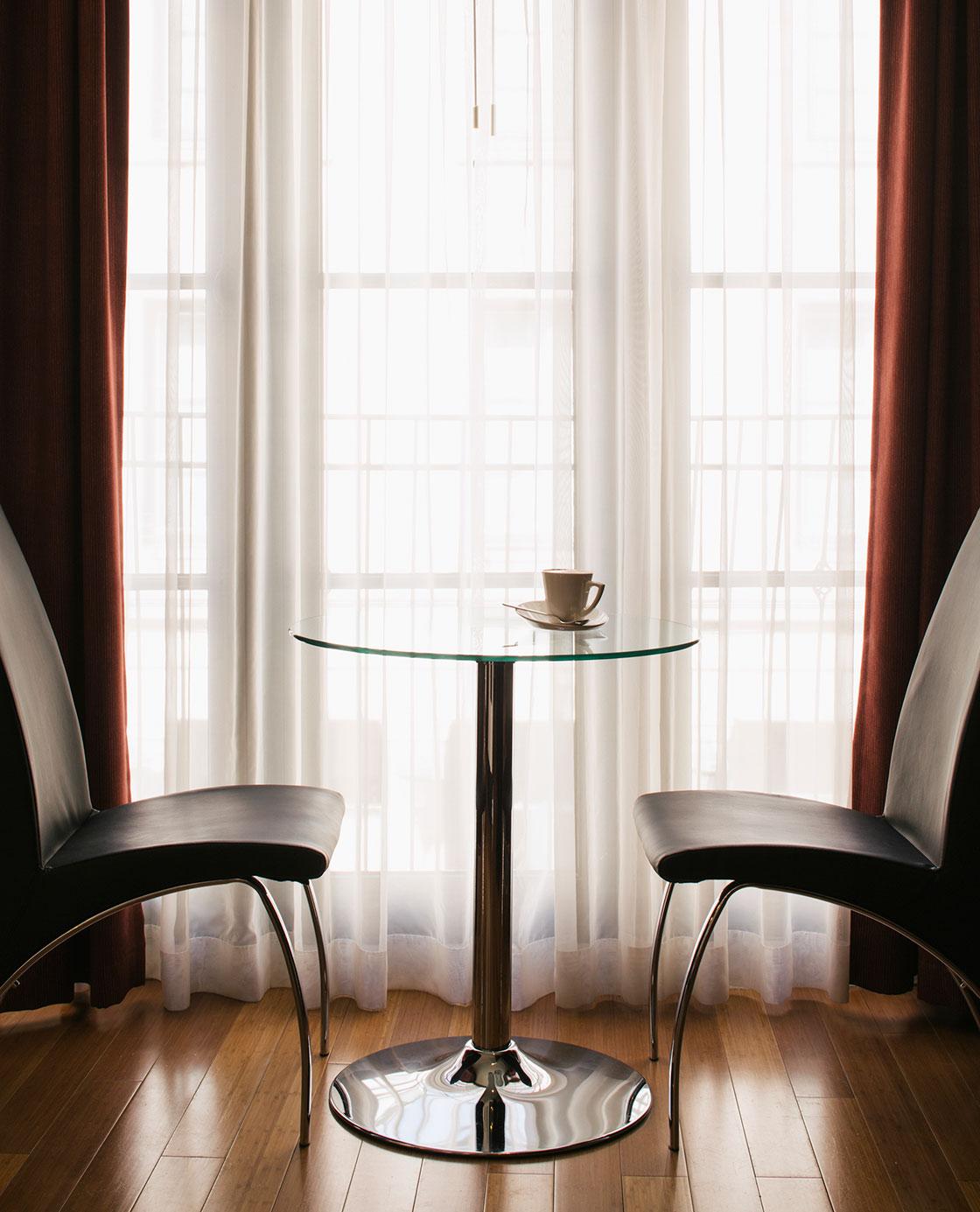 Deux chaises en face d'une table en verre avec un café posée sur la table.