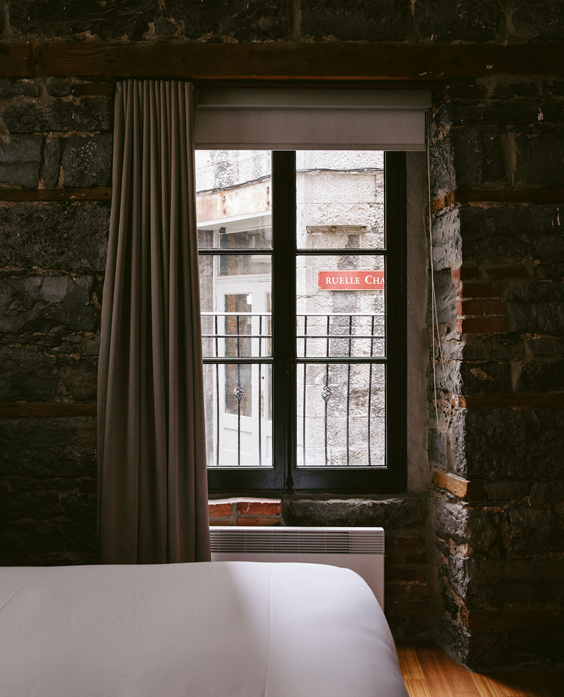 A bed beside a stone wall and a window.