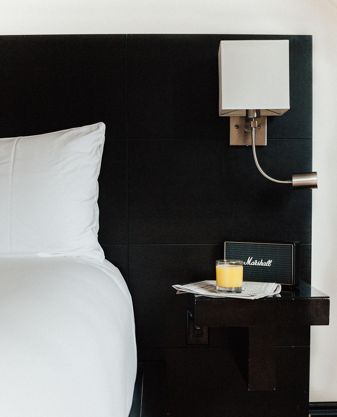 Un verre de jus d'orange, un journal et un poste radio posés sur une table de nuit près d'un lit d'une des chambres du Petit Hôtel.