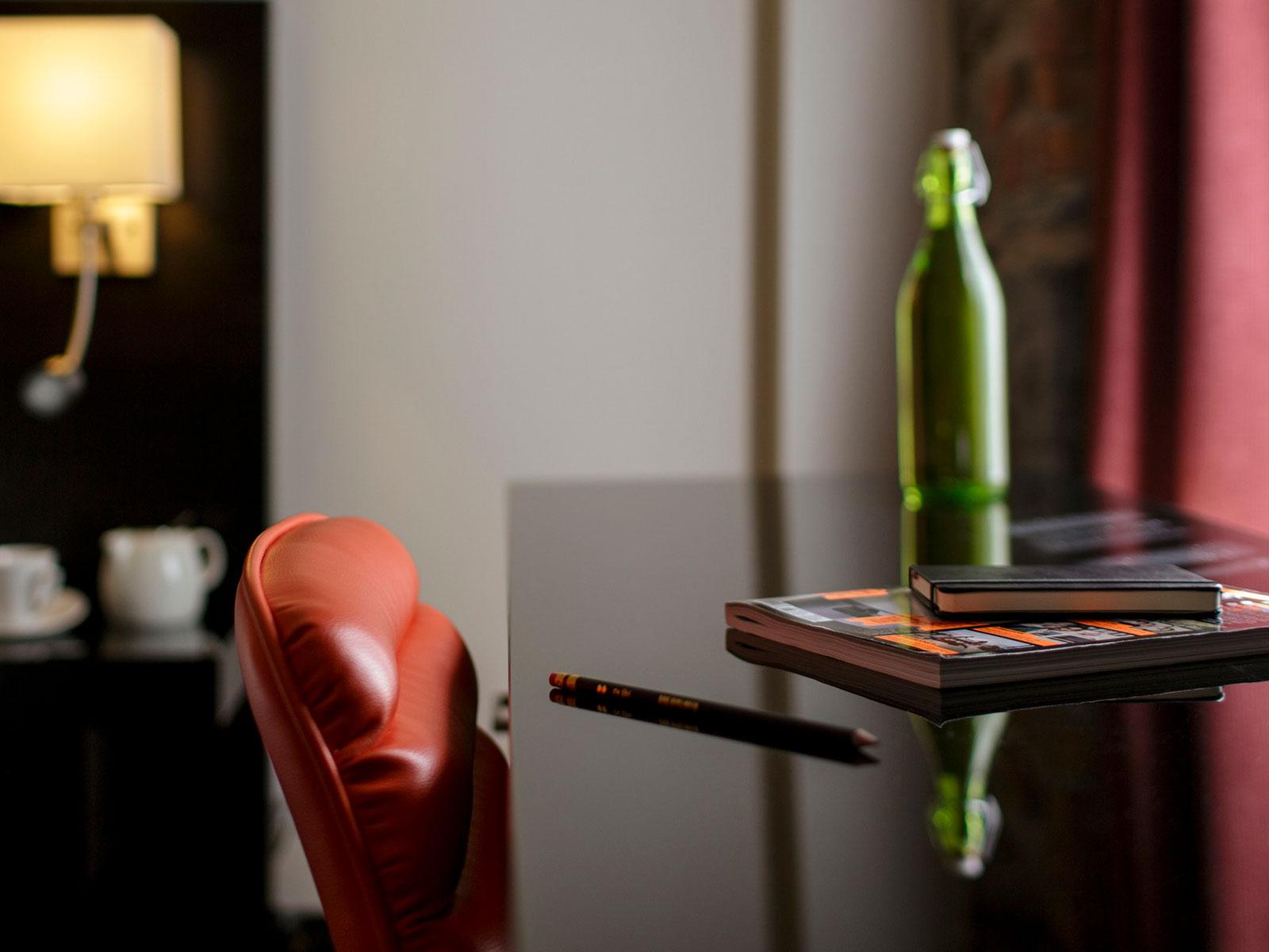 Une chaise orange et un bureau avec une bouteille et des carnets posés dessus.