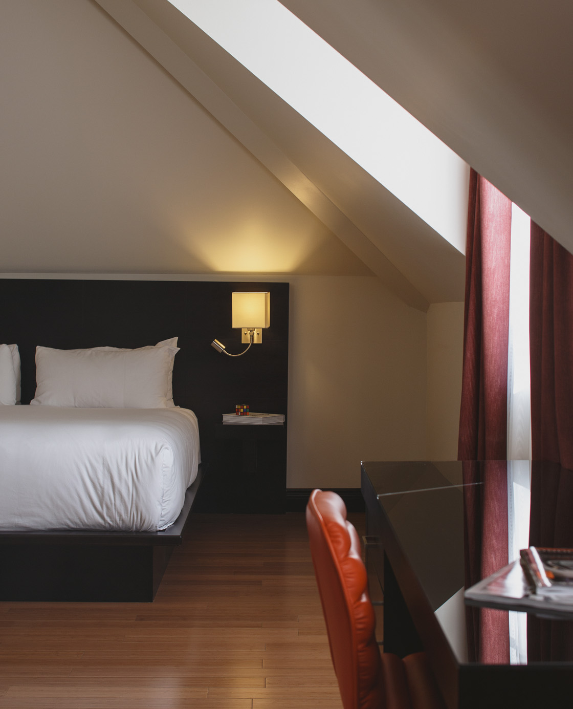 Un lit et une table et chaise de bureau dans l'une des chambres du Petit Hôtel.