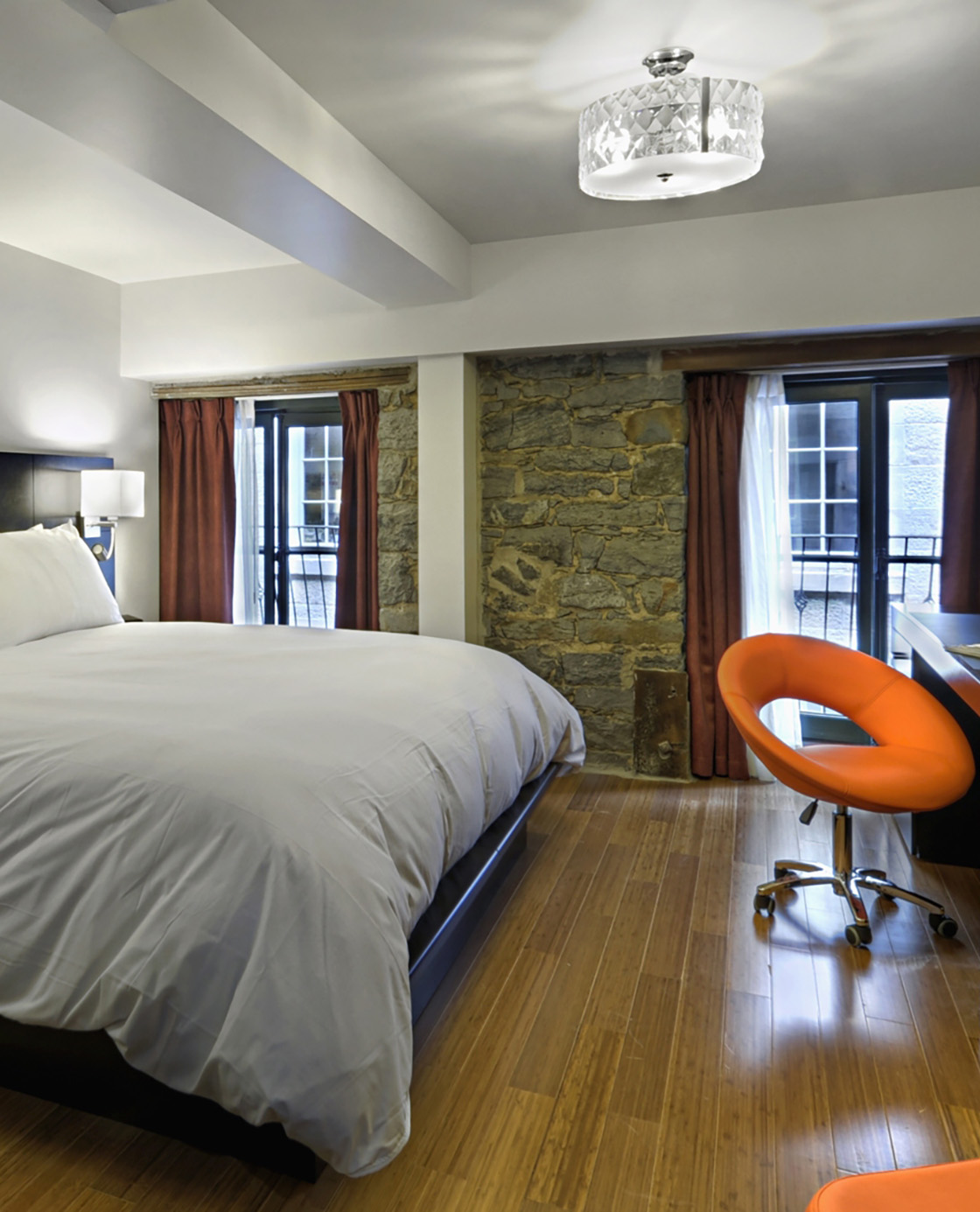 Un lit et un fauteuil orange avec une vue sur les fenêtres d'une des chambres du Petit Hôtel.