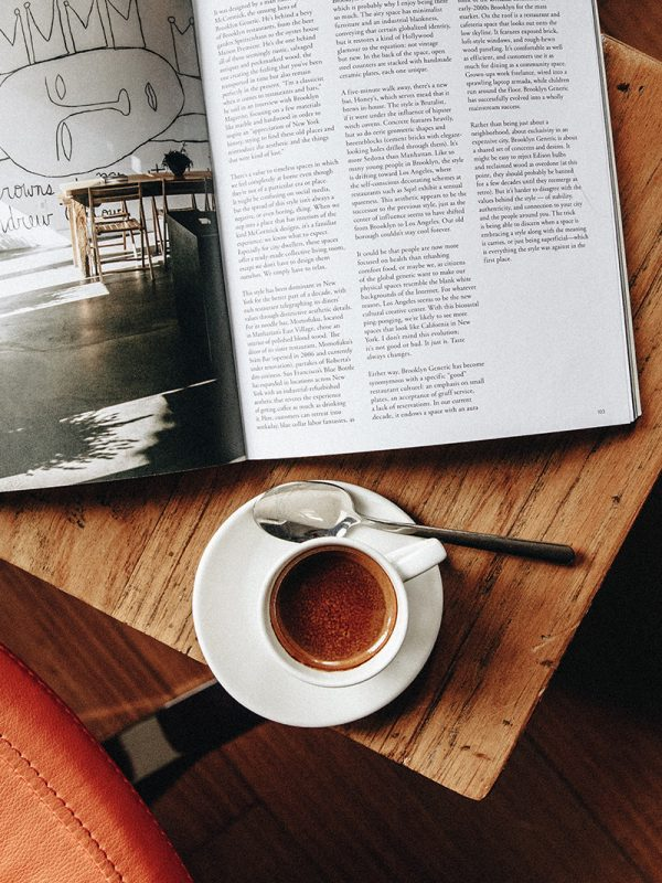 A coffee cup on a wooden table with an opened book