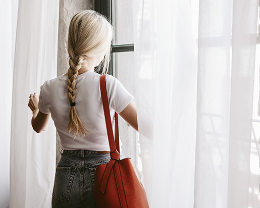 A blonde girl looking out the window of one of the rooms of Le Petit Hotel in Old Montreal